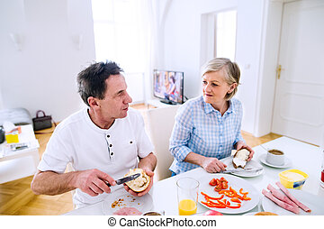 Senior man and woman having breakfast. Sunny morning. Table...