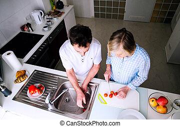 Senior man and woman preparing breakfast. Sunny morning.