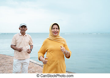 senior man and woman together running on the beach