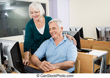 Senior Man And Woman Using Computer In Class