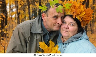 senior man and woman with leaves on head in park