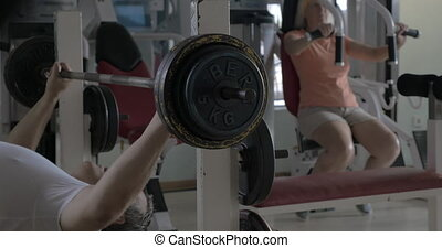 Senior man and woman working out in the gym