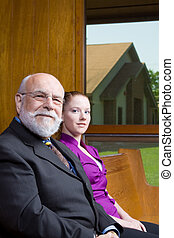 Senior man and young woman sitting in a church pew.  Looking at Camera.