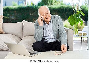 Senior Man Answering Smartphone At Nursing Home Porch -...