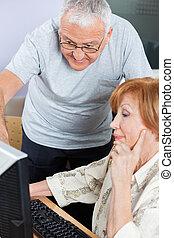 Senior Man Assisting Classmate In Using Computer