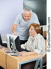 Senior Man Assisting Friend In Computer Class
