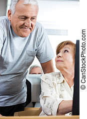 Senior Man Assisting Woman In Computer Class