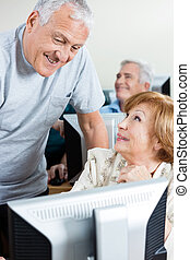 Senior Man Assisting Woman In Using Computer