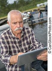 senior man at fishery using tablet