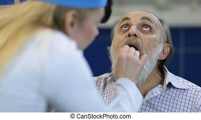 Senior man at the physician checking his throat - Senior ill...