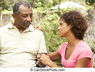 Senior Man Being Consoled By Adult Daughter