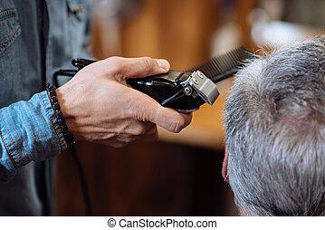 Senior man being trimmed at barbershop