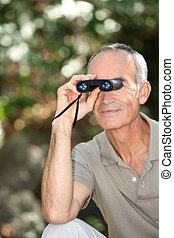 Senior man bird watching with binoculars