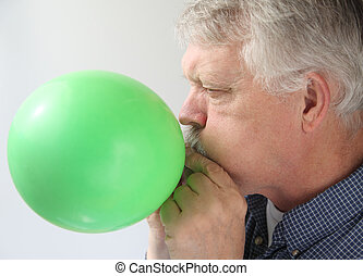 a man blows up a green balloon