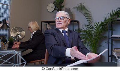 Irritated elderly man boss raising hands in questioning gesture why what in office room. Senior entrepreneur freelancer dissatisfied with bad results of work reviewing report and documents with errors