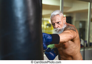 Senior man boxer training hard - Elderly male boxing in sport gym center club - Health fitness and sporty activity concept