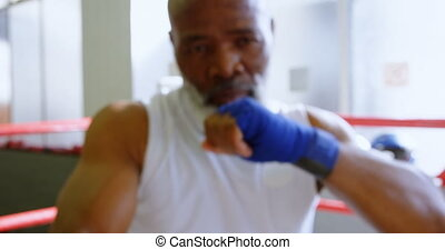 Senior man boxing in the fitness studio 4k