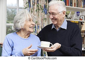 Senior Man Bringing Wife Cup Of Tea