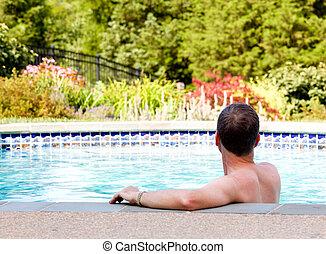 Senior man by edge of swimming pool