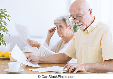 Senior man calculating household costs