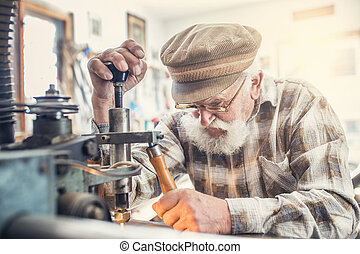 Senior man carving letters into marble plaque