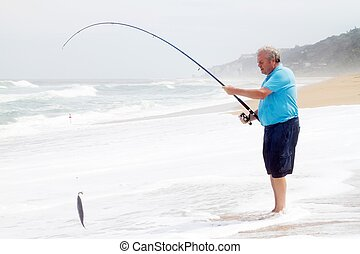 senior man catching a fish with fishing rod