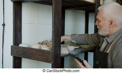 Senior man ceramist working with tablet doing inventory in ...