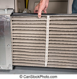 Senior man changing a dirty air filter in a HVAC Furnace -...
