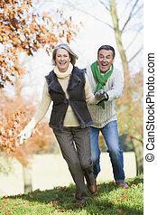 Senior man chasing woman through countryside