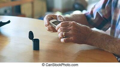 Senior man checking blood sugar on glucometer 4k - Senior ...