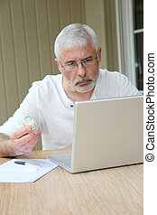 Senior man checking medical information on internet