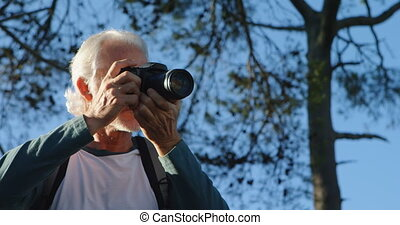 Senior man clicking photos with digital camera 4k - Senior...