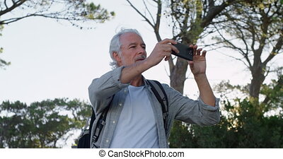 Senior man clicking photos with mobile phone at countryside...