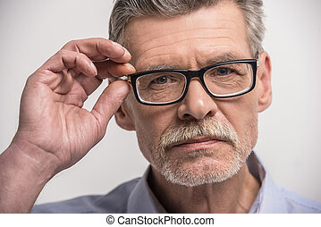 Senior man - Close-up. Senior male in glasses on grey ...