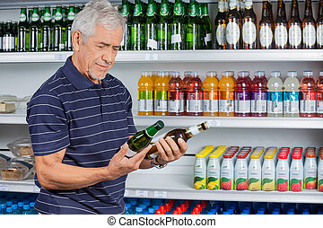 Senior Man Comparing Beer Bottles