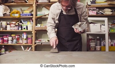 Senior man covering a surface with cement - Senior man...