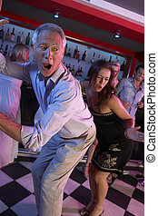 Senior Man Dancing With Younger Woman In Busy Bar