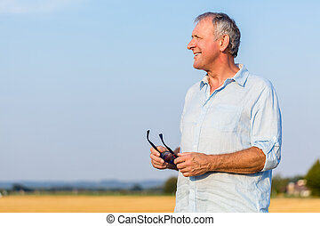 Senior man daydreaming outdoors in the countryside in a sunny da