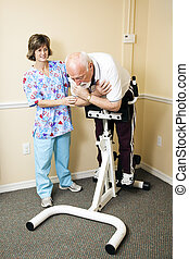 Senior Man Does Spine Stretch - Caring physical therapist in...