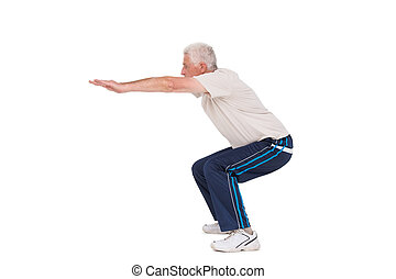 Senior man doing a squat on white background