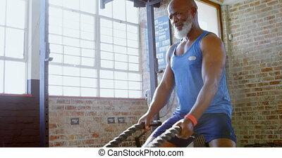 Senior man doing crossfit rope training in the fitness studio 4k
