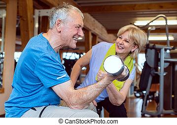 Senior man doing dumbbell exercise in the gym