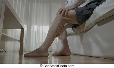 Senior man doing himself massage therapy on his tired legs relieve the pain and stress at home