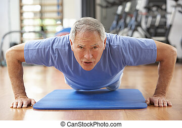 Senior Man Doing Press Ups In Gym