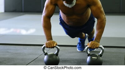 Senior man doing push-up with kettlebell in fitness studio ...