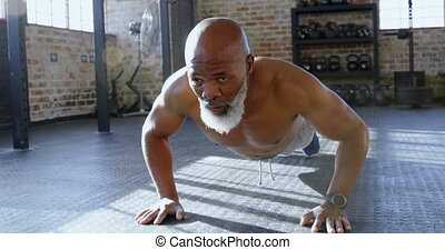 Senior man doing push ups in the fitness studio 4k