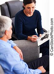 senior man doing Rorschach inkblot test with therapist