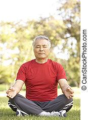 Senior Man Doing Yoga In Park