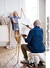 senior man drawing portrait of smiling woman in art workshop