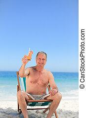 Senior man drinking a cocktail on the beach